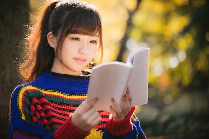 公園で読書する若い女性