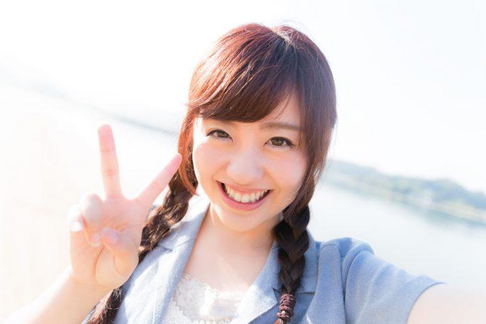ピースサインで自撮りする若い女性の笑顔